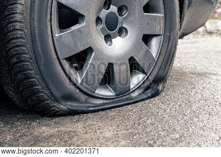flat car tire close up, punctured wheel