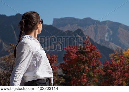 Young Woman In Sunglasses Admires Large Rocky Hilltops Of Brown Colour And Red Trees Under Clear Blu