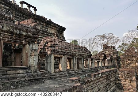 Ancient Temple Of Baphuon, In Angkor. Stone Terraces, Empty Window Openings, Damaged By Time. The Wa