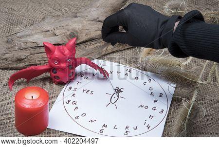 Fortuneteller's Black Gloved Hand Holding Needle. Spiritualism Ritual. Burning Candle, Bat And Magic