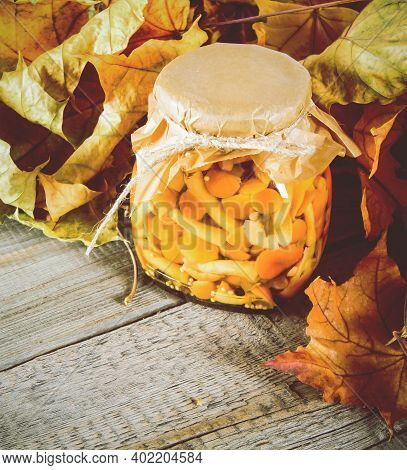 Autumn Concept. Preserved Food In Glass Jar On A Wooden Board. Marinated Mushrooms