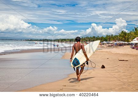 BALI, INDONESIA - JANUARY 13: Unidentified young man with surf board on January 13, 2012. Dreamland beach, Bali, Indonesia. The Dreamland is one of the most popular surfing areas of Bali.