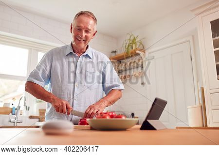 Retired Man Making Meal In Kitchen Asking Smart Speaker In Foreground Question