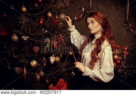 Portrait of a beautiful red-haired woman magician standing with a magic wand in her hand by a Christmas tree. Beautiful fairy christmas decoration. Christmas fairy tales.
