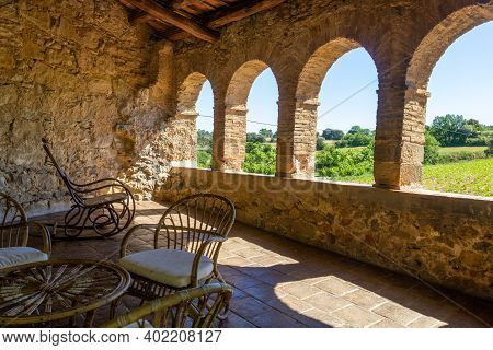 Open Terrace With A Wicker Table And Some Wicker Chairs With A View To To The Green Landscape On A S