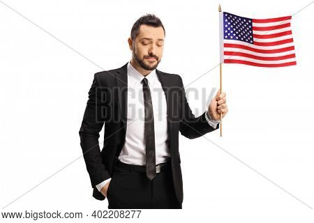 Disappointed businessman holding a USA flag and looking down isolated on white background