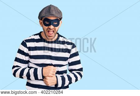 Young handsome man wearing burglar mask smiling and laughing hard out loud because funny crazy joke with hands on body.
