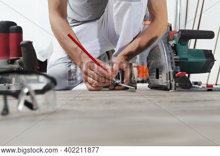 Man Worker Hands Installing Timber Laminate Floor, Takes Measurement With The Tape Measure And Penci
