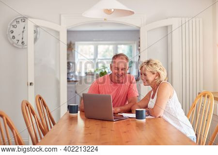 Retired Couple At Home In Kitchen Using Laptop To Shop Online Or Make Video Call