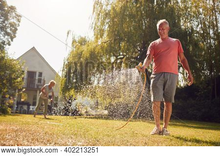 Retired Couple At Work Watering Plants With Hose And Tidying Garden With Rake At Home