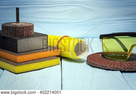 Abrasive Tools And Goggles On Blue Wooden Boards. These Tools Are Used To Grind Objects