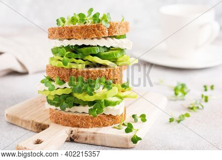 Avocado, Cucumber And Feta Cheese Sandwich Decorated With Micro-greens And Multi-grain Bread On A Si