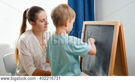 Little Smiling Boy Learning Abc With Young Mother At Home. Teacher Writing Alphabet On Blackboard Wi