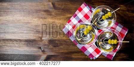 Drink Martini. Three Martini With Olives On A Wooden Table. Free Space For Text. Top View
