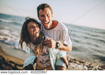 Young Woman Giving Piggyback Ride To Boyfriend On Beach.
