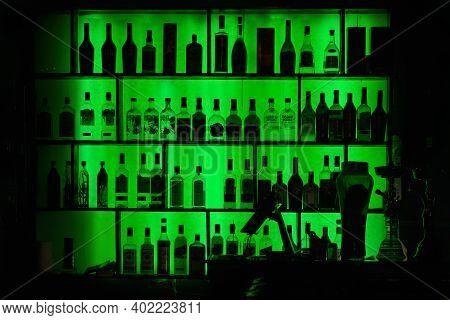 Bottles Of Alcohol And Spirits At Bar Or Pub Shelves With Green Backlit. Bar Background.  Vietnam, H