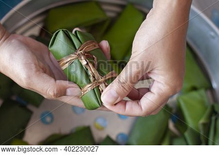 Hand Holding Raw Steamed Sticky Rice With Banana Or Thai People Call Khao Tom Mud Which Is Being Pre