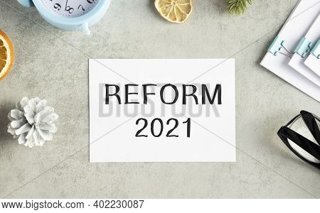 The Text Reform 2021 On Office Desk With Alarm Clock, Markers, Glasses And Financial Charts.