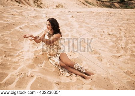 Woman Sitting On Desert Sand And Holding Spreading Sand In Hand.