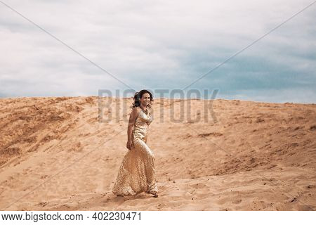 Woman In Dress Walking In The Sand Of Desert Dunes With Steps In The Desert Sand, Young Woman Walkin