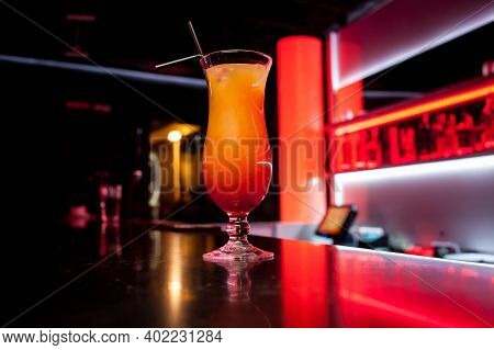 Alcoholic Orange Cocktail Is On The Bar. Glass Of Cocktail On Bar Background. Fresh Cocktail With Or