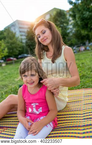Woman Mom In Summer In Park Sits On A Blanket, Straightens Her Hair For A Little Girl Daughter 5-6 Y