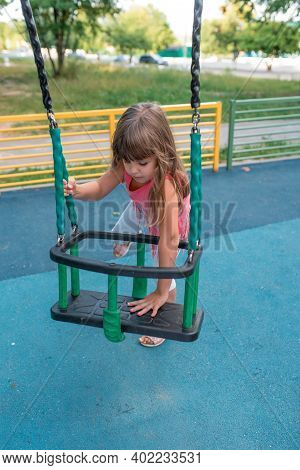 Little Girl 5-7 Years Old, In Summer On Playground, Sit Down And Climb Off Swing, Rest In Summer On
