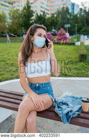 Female Woman City Summer Medical Mask, Sits On Bench, Talks On Phone, Listens Voice Message, Online