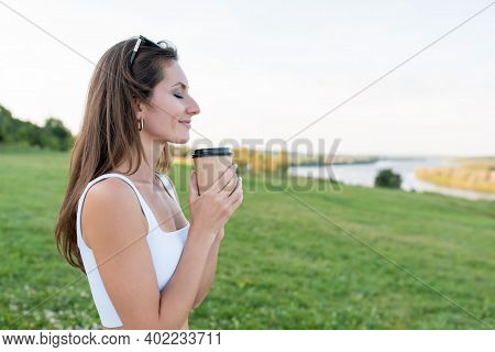 Happy Woman In Summer Park Holds Cup Coffee Tea In Hands, Free Space For Text Copy, Landscape Meadow