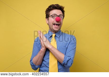 Handsome Young Man With Red Clown Nose Smiling And Clapping Hands.