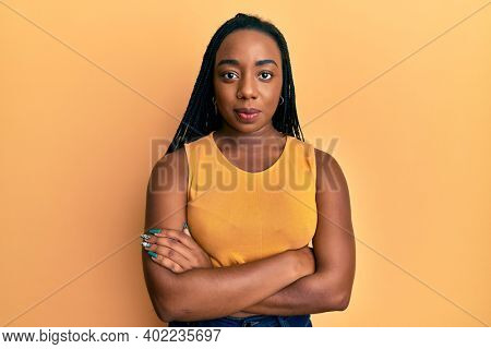 Young african american woman with arms crossed gesture relaxed with serious expression on face. simple and natural looking at the camera.