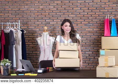 Beautiful Asian Woman Standing Among Several Boxes And Checking Parcels, Working In The House Office