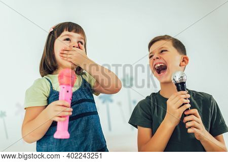 Family At Home. Portrait Of A Happy Children Singing Karaoke Through Microphone At Home.