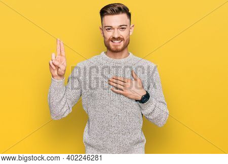 Young redhead man wearing casual winter sweater smiling swearing with hand on chest and fingers up, making a loyalty promise oath