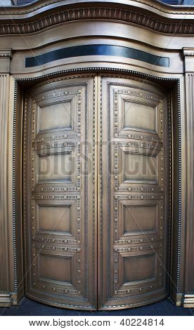 Large curved brass closed doors on a bank entrance poster
