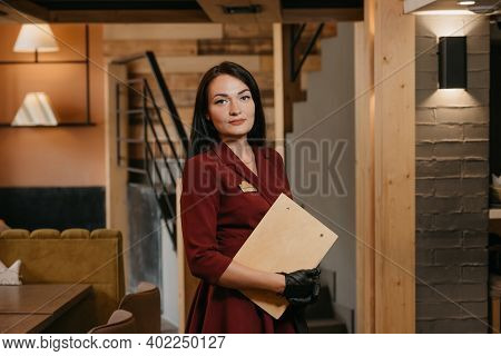 A Female Restaurant Manager In Black Disposable Medical Gloves Is Posing Holding A Wooden Menu In A