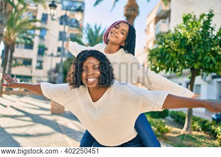 Beautiful african american mother giving daughter piggyback ride with open arms at the park.