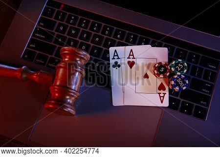Law For Online Casino. Wooden Judge Gavel And Aces On Keyboard Of Laptop