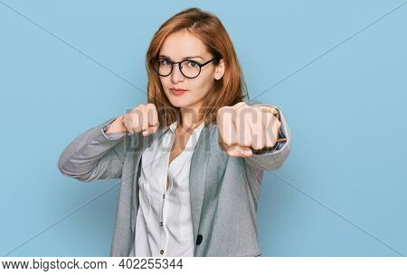 Young caucasian woman wearing business style and glasses punching fist to fight, aggressive and angry attack, threat and violence