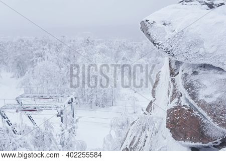 Frosty Rock In The Background Of The Last Tower Of The Ski Lift On A Snow-covered Hilltop Among Fros