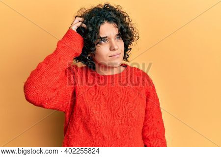 Young hispanic woman with curly hair wearing casual winter sweater confuse and wondering about question. uncertain with doubt, thinking with hand on head. pensive concept.