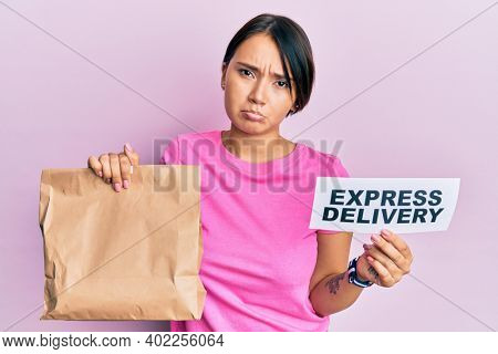 Beautiful young woman with short hair holding paper pag with express delivery text depressed and worry for distress, crying angry and afraid. sad expression.