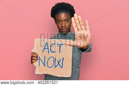 Young african american girl holding act now banner with open hand doing stop sign with serious and confident expression, defense gesture
