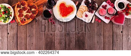 Home Cooked Valentines Day Dinner. Overhead View Top Border Against A Dark Wood Banner Background. H