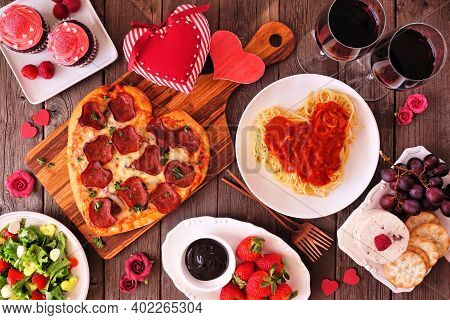 Home Cooked Valentines Day Dinner. Top View Table Setting On A Dark Wood Background. Heart Shaped Pi