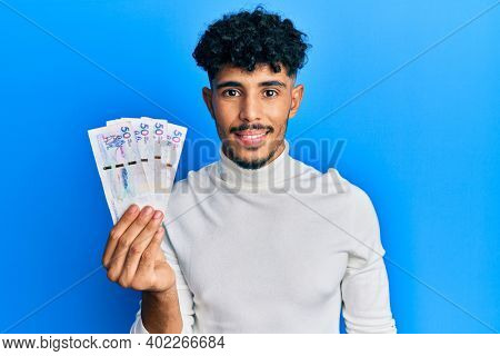 Young arab handsome man holding 50 colombian pesos banknotes looking positive and happy standing and smiling with a confident smile showing teeth