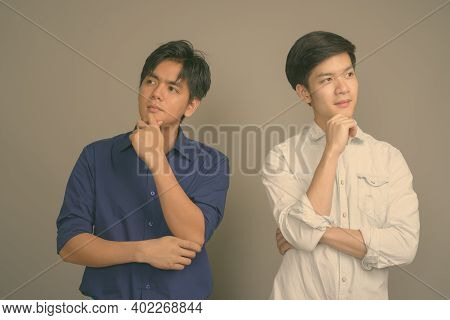 Two Young Handsome Asian Men Against Gray Background