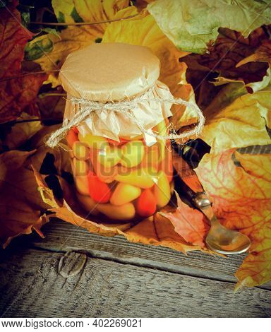 Autumn Concept. Preserved Food In Glass Jar On A Wooden Board. Marinated Hot Pepper