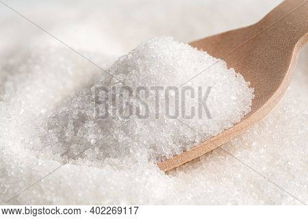 Wooden Spoon Full Of Refined Granulated Sugar On Top Of Refined Granulated Sugar.