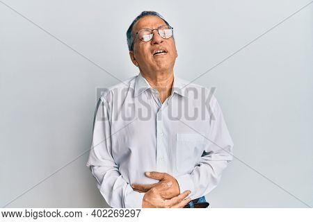 Middle age indian man wearing casual clothes and glasses with hand on stomach because nausea, painful disease feeling unwell. ache concept.